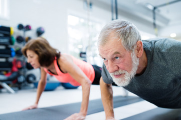 Fototapeten Fitness Senior couple in gym working out, doing push ups