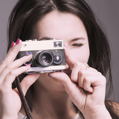 Pretty young woman photographed with retro film camera