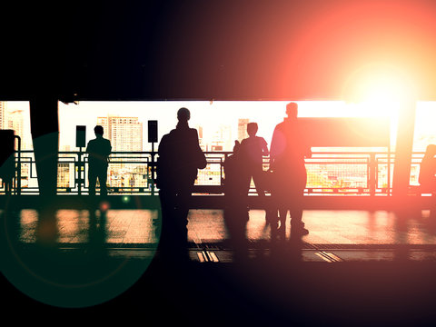 Silhouette of people waiting at train's platform with backlight