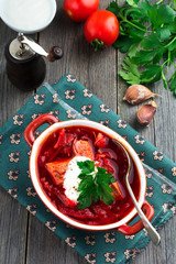 Beetroot soup with meat, sour cream and parsley in a brown ceramic bowl on the old wooden background. Borsch- traditional dish of Ukrainian cuisine. Selective focus.Top view.
