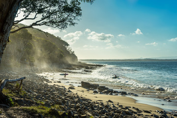 Tropical Surfer Beach. Idyllic sunset at famous Tea Tree Bay, Noosa, Australia. Sun shining through spray mist in the eucalyptus trees. Tropical stone pebbles in the foreground. Two surfers ret