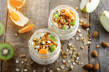 Yogurt, granola and fruits in a jars for delicious breakfast. Traditional American healthy food. Top view Instagram style photo.