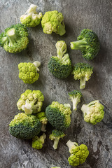 Ripe green broccoli and cauliflower. Grey stone background. Top