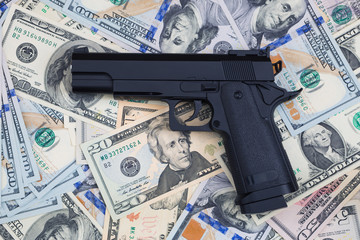 Gun on money background