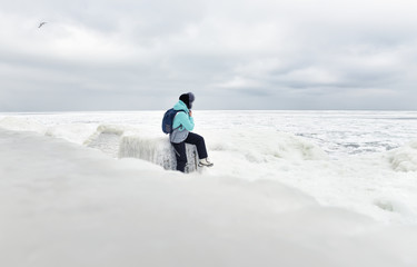 frozen, ice-covered sea, large snow drifts and ice floes on the beach, a lone man sitting on the beach. snow-white expanse of ice