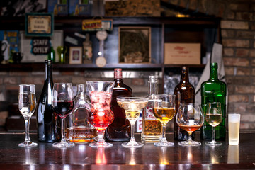 many different bottles of alcohol in different shapes, glasses with alcohol of various shapes, on the bar