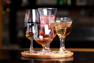 glasses of different shapes with different alcohol on a wooden round board on the bar