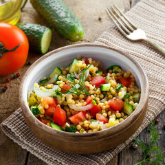 Traditional Israeli healthy meal Ptitim with tomatoes, cucumber and onion for delicious healthy breakfast. Classic Moroccan couscous with vegetables. Top view.