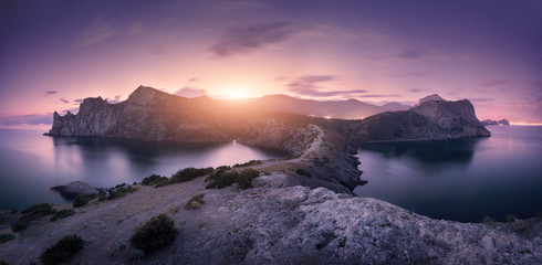 Wall Mural - Beautiful mountains against colorful cloudy sky at sunset. Landscape with rocks, sea, mountain trail, forest, purple sky and city lights in summer. Nature and travel. Blurred clouds. Panoramic view