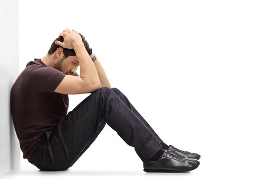 Depressed man sitting on the floor with his head down