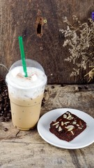 Ice Cappuccino Coffee and sweet chocolate brownies. A cup of latte, cappuccino or espresso coffee with milk put on a wood table with dark roasting coffee beans. Drawing the foam milk on top.