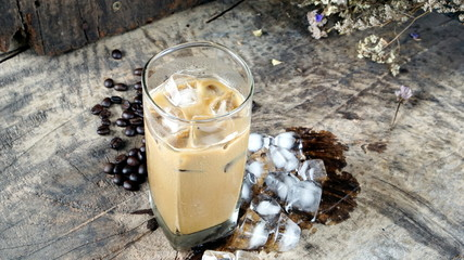Ice Cappuccino Coffee. A cup of latte, cappuccino or espresso coffee with milk put on a wood table with dark roasting coffee beans. Drawing the foam milk on top.