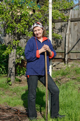 Woman is standing with rake near pole and pear tree.