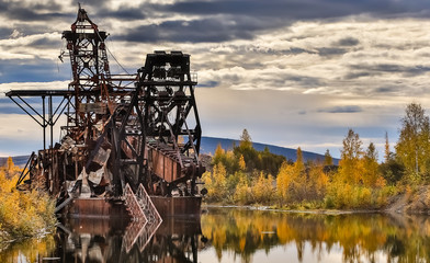 Remains of historic Gold Dredge No 3 in fall with reflections on the lake, Steese Highway, Alaska
