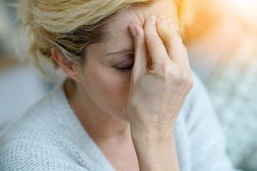 Portrait of middle-aged blond woman having a migraine