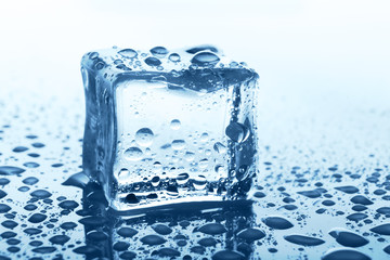 Transparent ice cube with reflection on blue glass with water drops