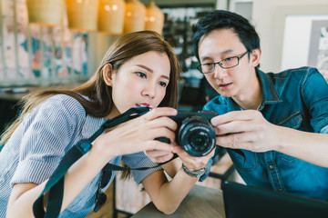 Young Asian couple learning to use mirrorless digital camera together at coffee shop, modern gadget technology concept, focus on the girl, depth of field effect