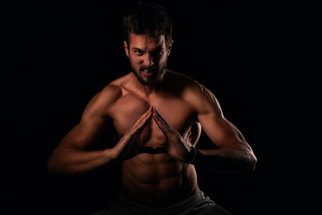 Young man with muscular body showing his strength