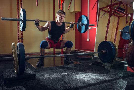 Teenage man doing squats indoor.