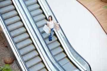 Female shopaholic moving downwards on escalator