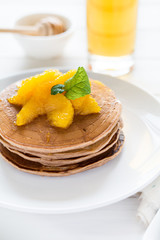 Traditional breakfast: stack of pancakes with orange slices and sweet sauce on white wooden table. Selective focus
