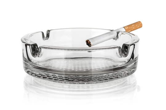 Glass ashtray with cigarette isolated on white