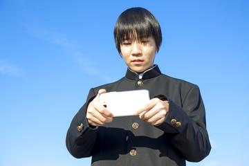 学ラン姿でスマホを操作する高校男子