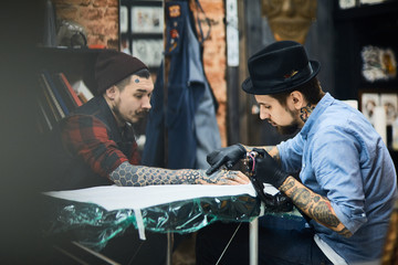 Master of tattooing and his client in salon