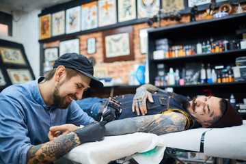 Happy young tattooer in ball-cap working with client