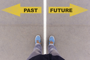 Past and future text arrows on asphalt ground, feet and shoes on Wall mural