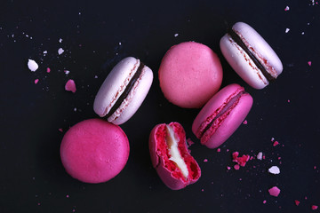 Macaroons on dark background, colorful french cookies macarons. The broken macarons with crumbs. Gift for Valentine's Day and 8 March International Women's Day