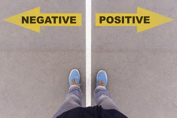 Negative vs Positive text arrows on asphalt ground, feet and sho