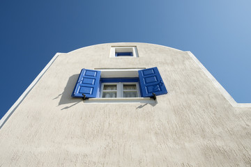 Blue shutters open on a window with blue sky in Akrotiri, Santorini island