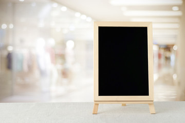 Blank chalkboard standing on sack tablecloth over blur store wit