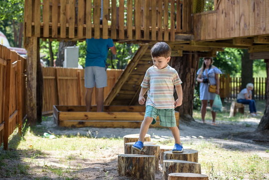 Little boy climbing on a wooden playground in rope park. Kid play outdoors warm sunny summer day