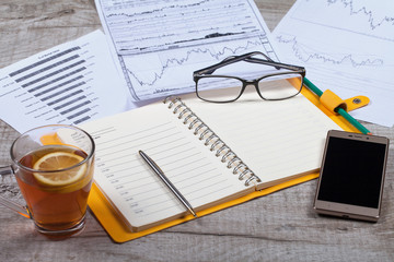 Top view of open notebook, glasses, a cup of tea, pen and smartphone on a wooden table