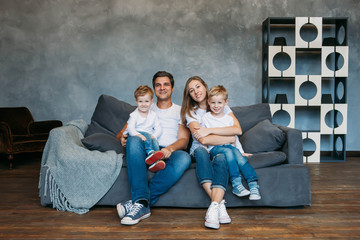 Children draw markers on floor while parents relax couch