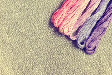 Set for embroidery. Embroidery thread shades of violet and pink color on linen homespun cloth. Coloring and processing photos. Shallow depth of field.