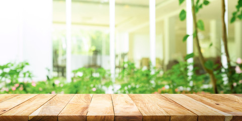 Empty wood table top on blur abstract green from garden and house  living room.