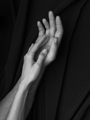 Black and white image, hands of man and woman tenderly touching each other on black background