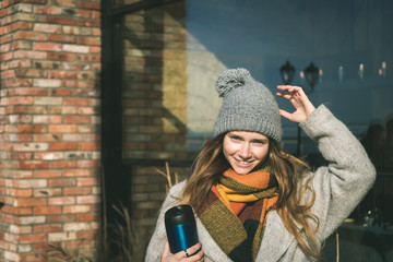 Happy teen in warm coat and hat, Thermocup in hand,sunny day outdoor