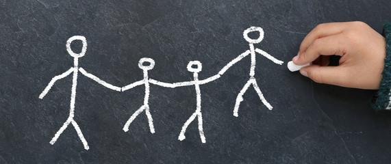 Enfant dessinant une famille à la craie sur une ardoise
