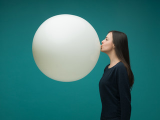 funny young woman with long dark hair inflating huge balloon on blue background Wall mural