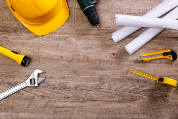 Helmet, screwdriver and flashlight. Construction design. Tape measure. Adjustable wrench, architecture plans and knife. Worker equipments on workplace.