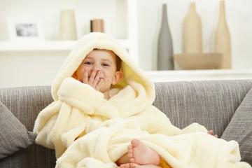 Happy smiling kid sitting in bathrobe at home sofa