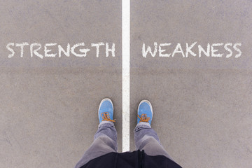 Strength and weakness text on asphalt ground, feet and shoes on Wall mural