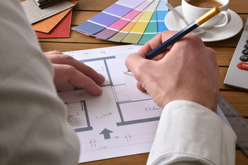 Designer writing on the plan of an interior design project
