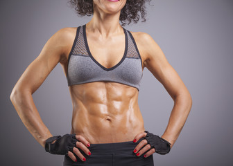 Cropped image of a fitness woman standing on gray background