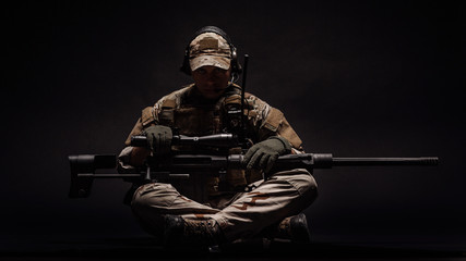 Portrait soldier or private military contractor holding sniper rifle