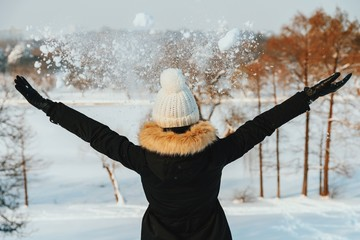 Girl Throwing Snow In Air During Winter